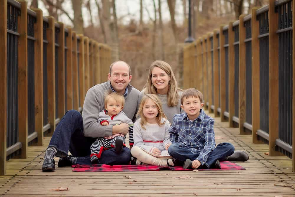 bradshaw family sits on a bridge at sharon woods during a family photo session