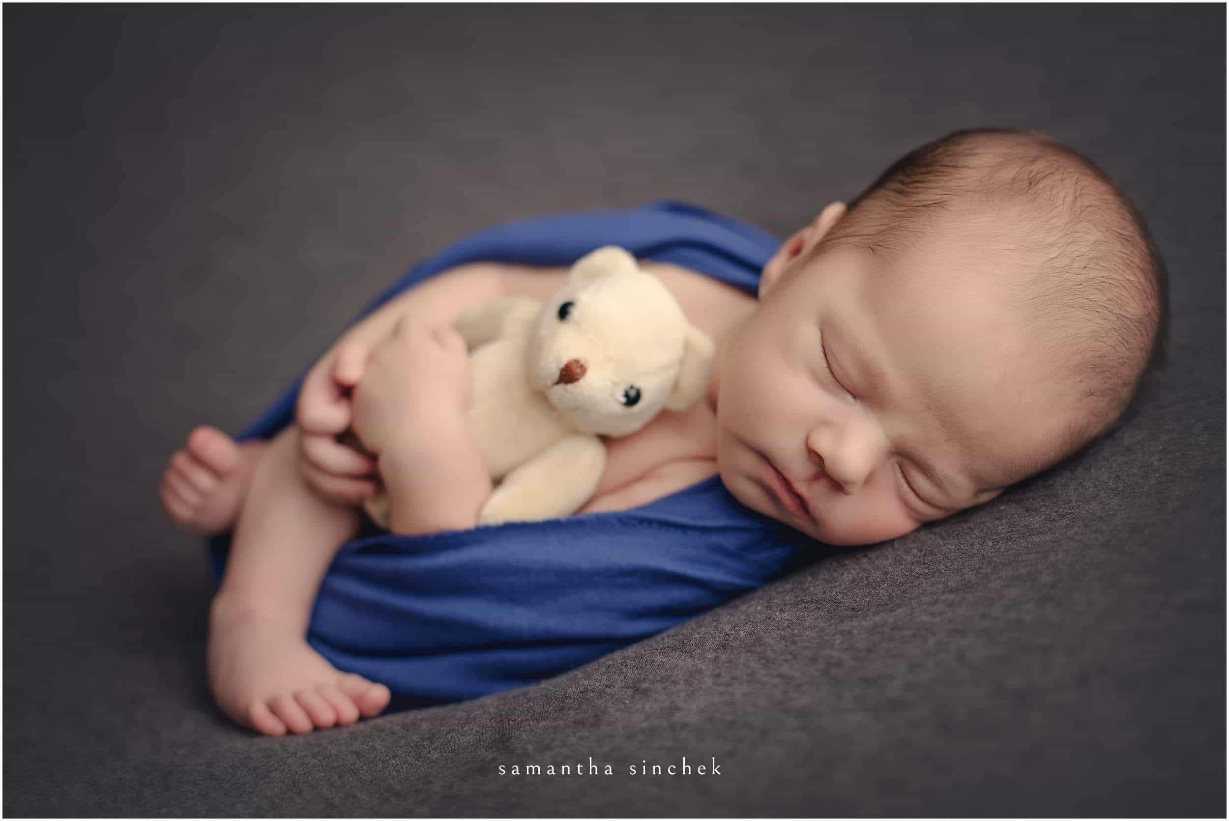 baby boy snuggles teddy bear at cincinnati newborn photographer studio