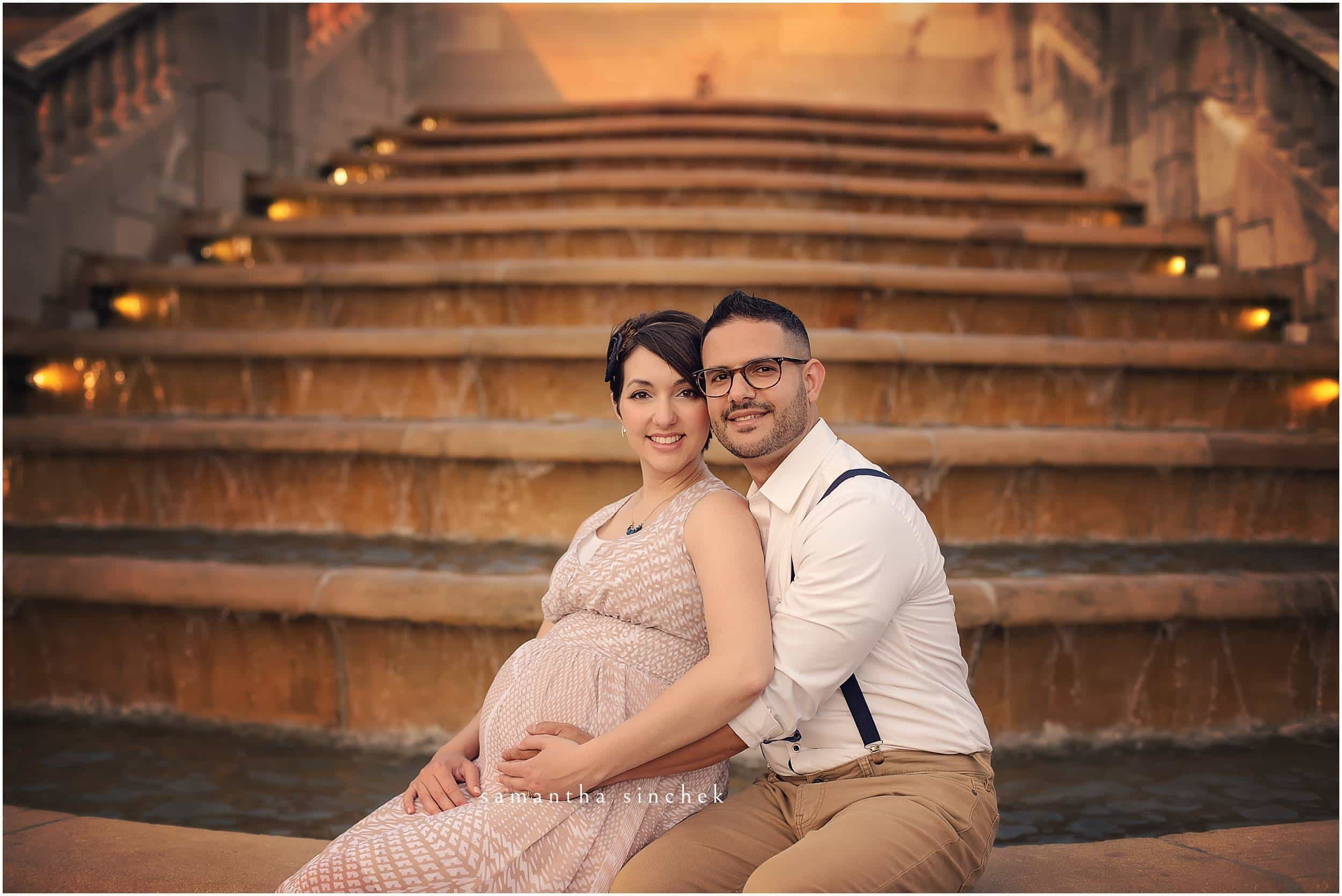 COUPLE SITS ON FOUNTAIN IN FRONT OF AULT PARK PAVILION