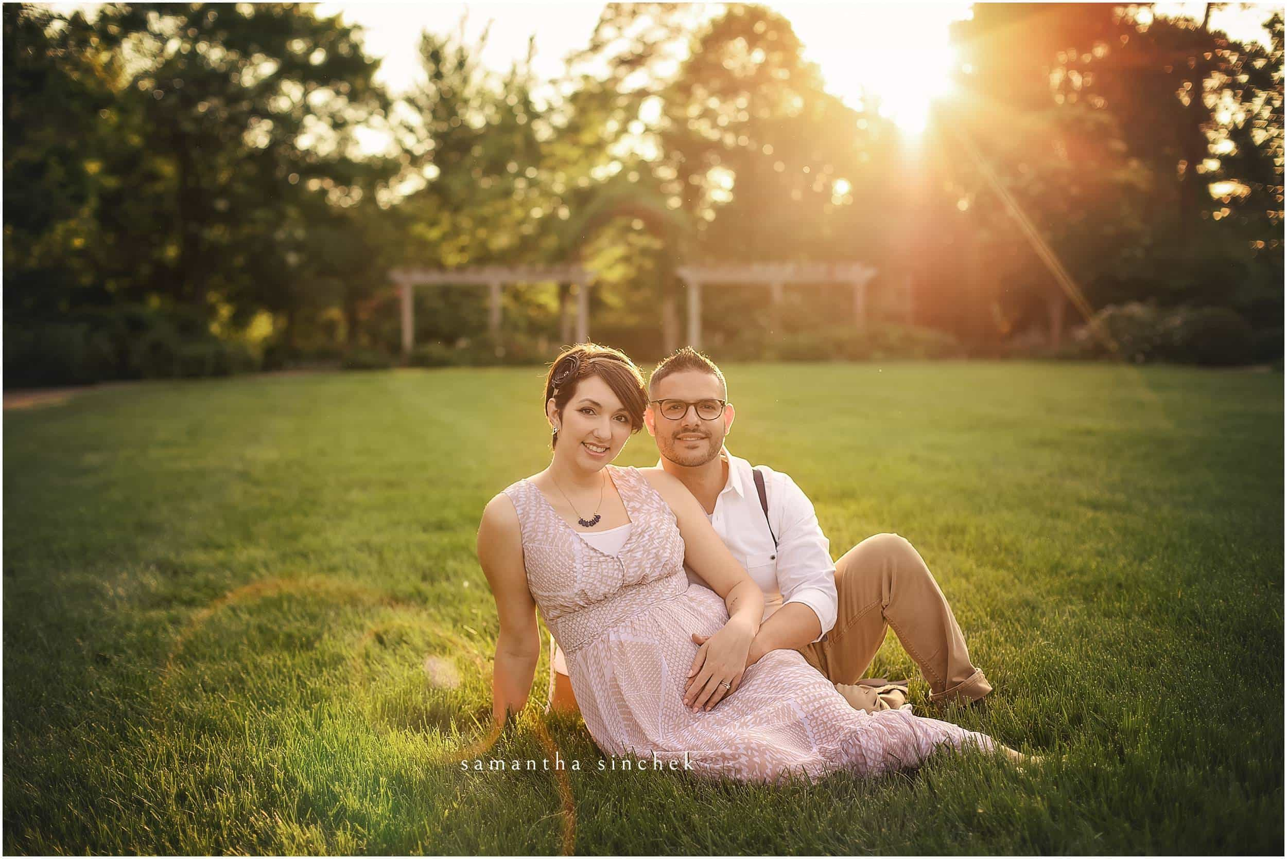 MATERNITY COUPLE SITS IN GRASS AT AULT PARK