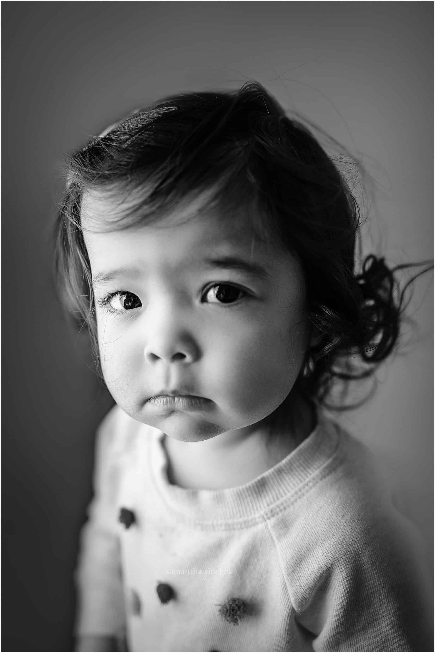 two year old stares at camera during newborn pictures for her sister