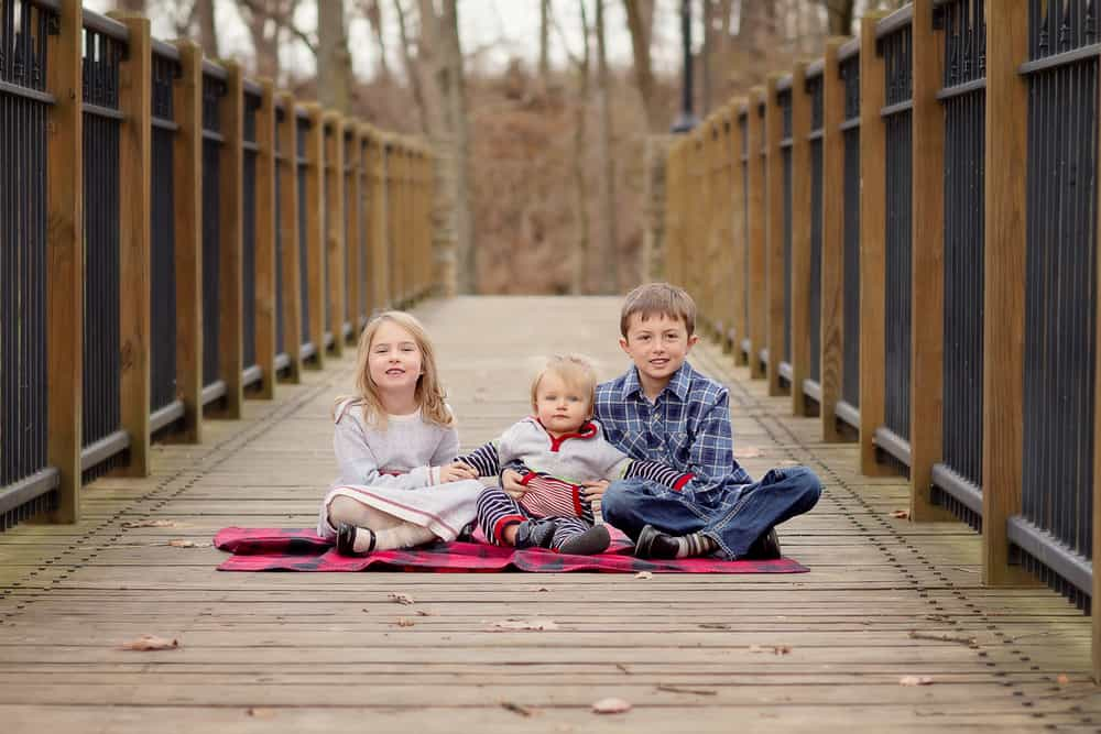three siblings sit together during family photo session at SHARON woods, CINCINNATI