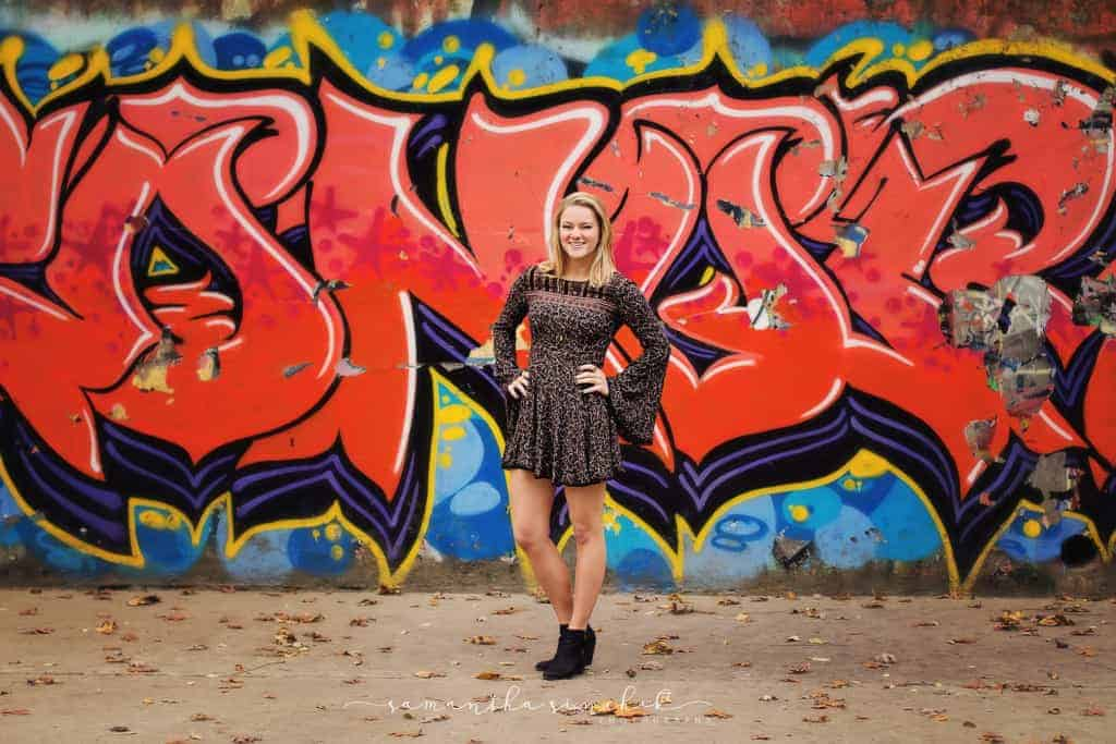 High school senior girl stands in front of graffiti wall