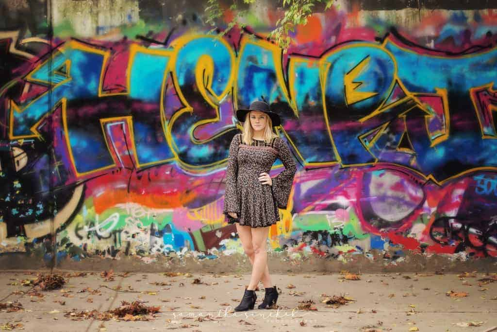 High school senior wearing black hat and stands in front of graffiti wall