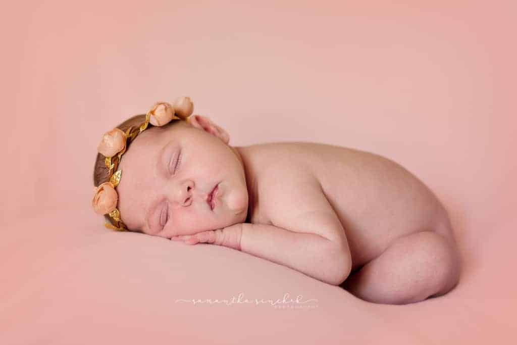 Baby girl from Cincinnati sleeps on pink fabric wearing pink and leather headband from target