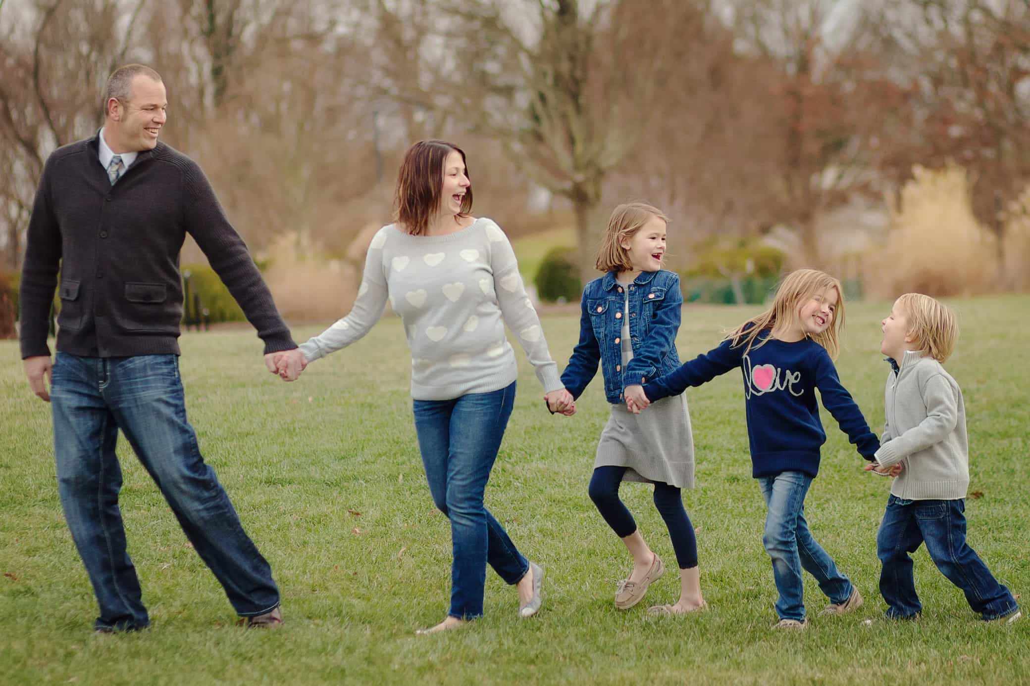Family walks hand in hand laughing and having fun