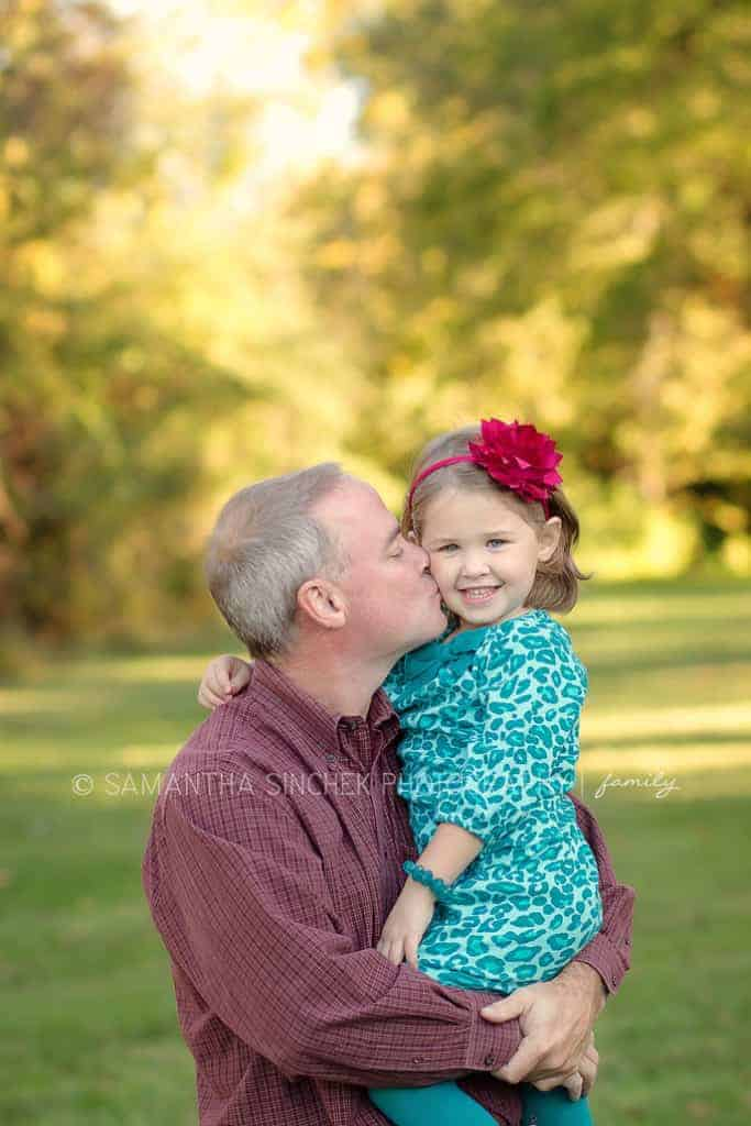 father kisses daughter on the cheek