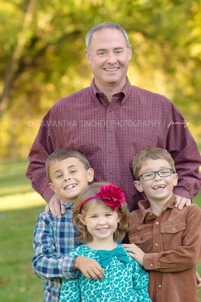 children poses for a photo with their father