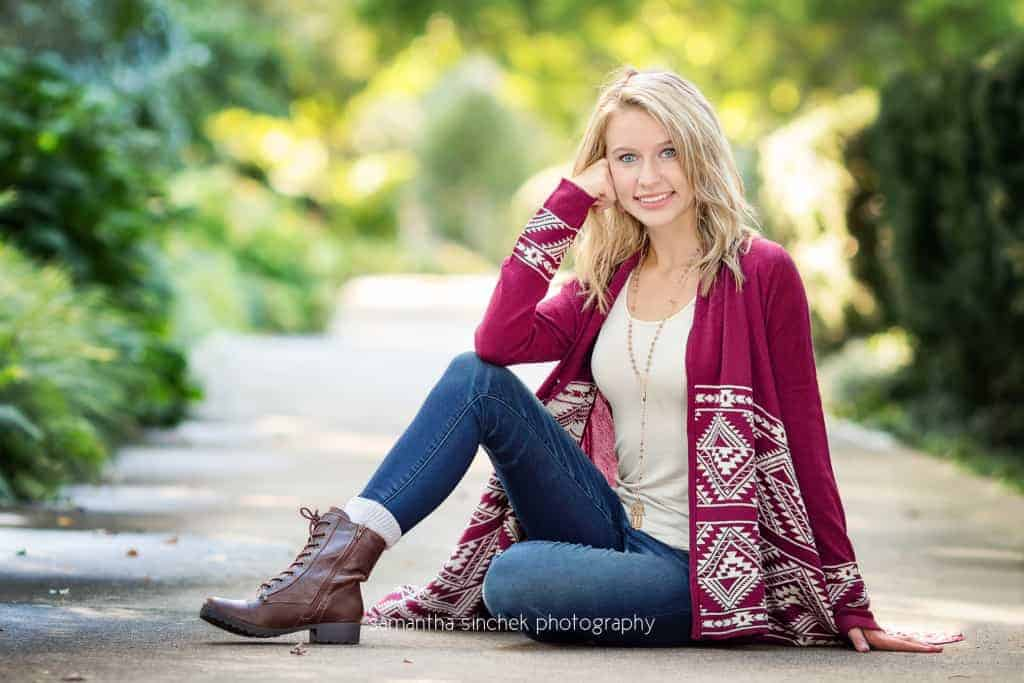senior girl wears jeans and sweater during senior photo session