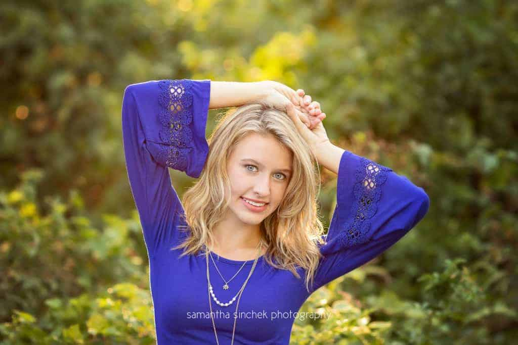 senior girl from kings high school wears blue dress with hands above her head