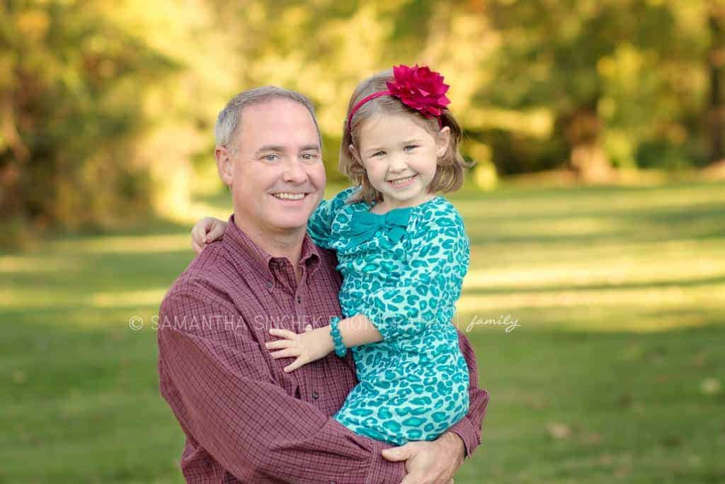 young girl smiles at camera in fathers arms