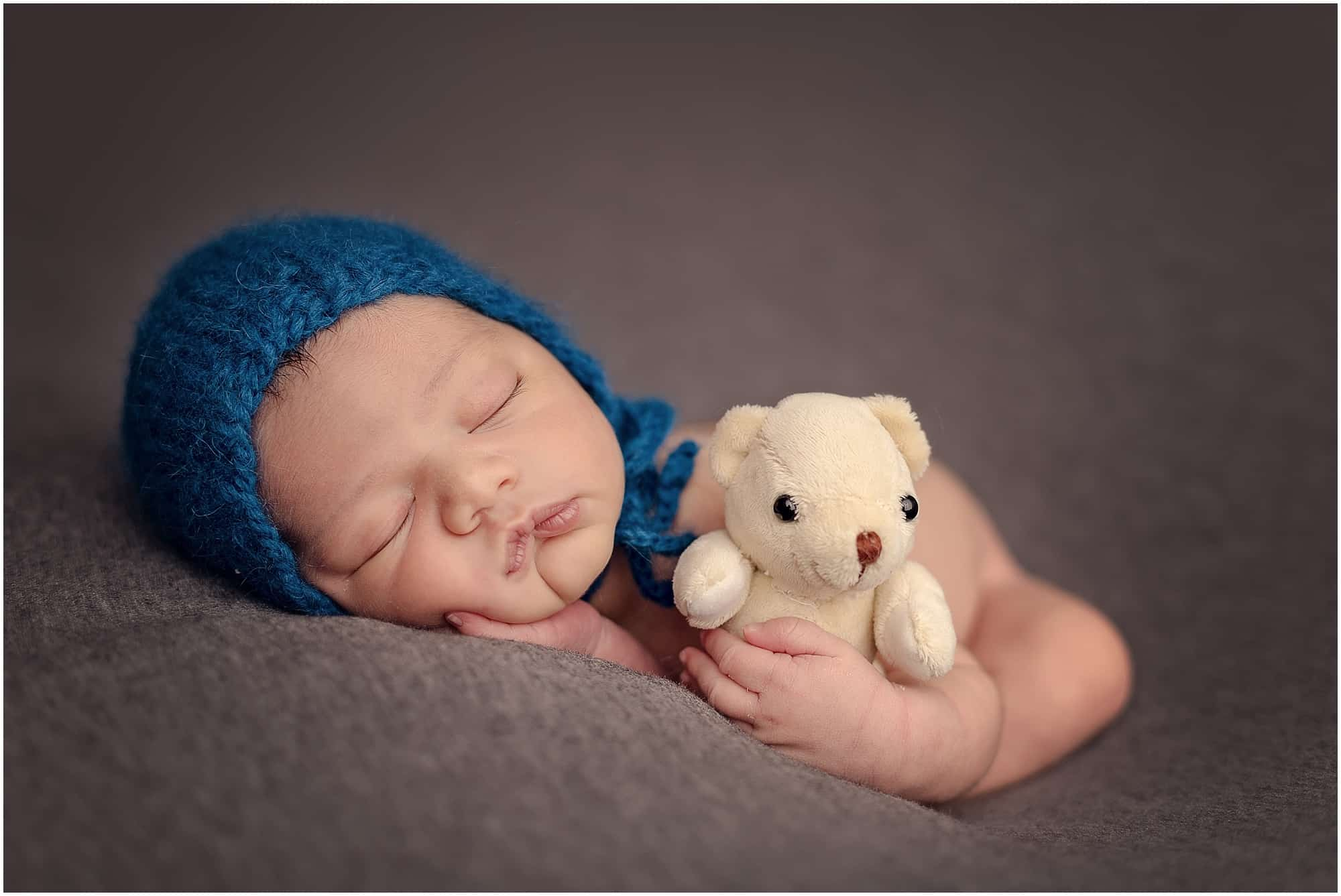 baby boy holds teddy bear at Cincinnati Ohio newborn session with Sinchek Photography