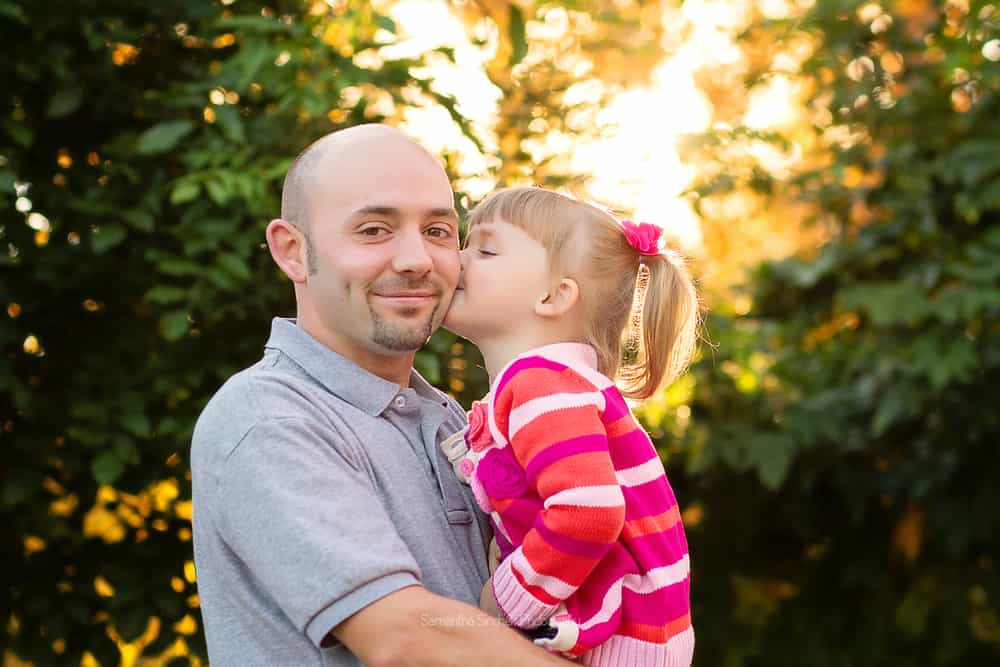 Young daughter kisses dad on the cheek