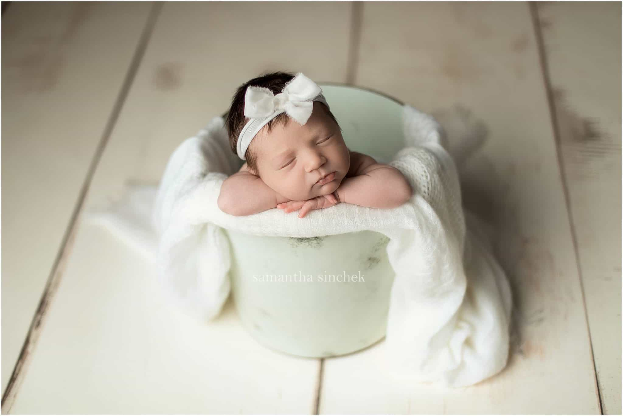 baby in a bucket with a white headband with cincinnati newborn photographer