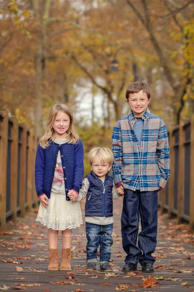 Three siblings hold hands during fall pictures at Sharon Woods