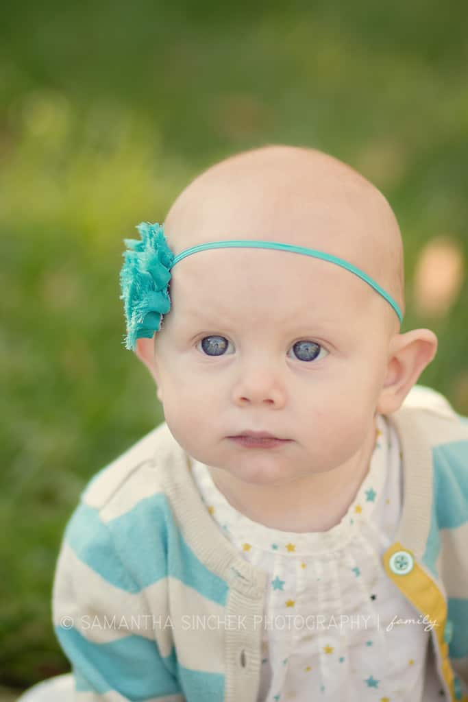 toddler girl with blue eyes smiles at Samantha sinchek photography camera