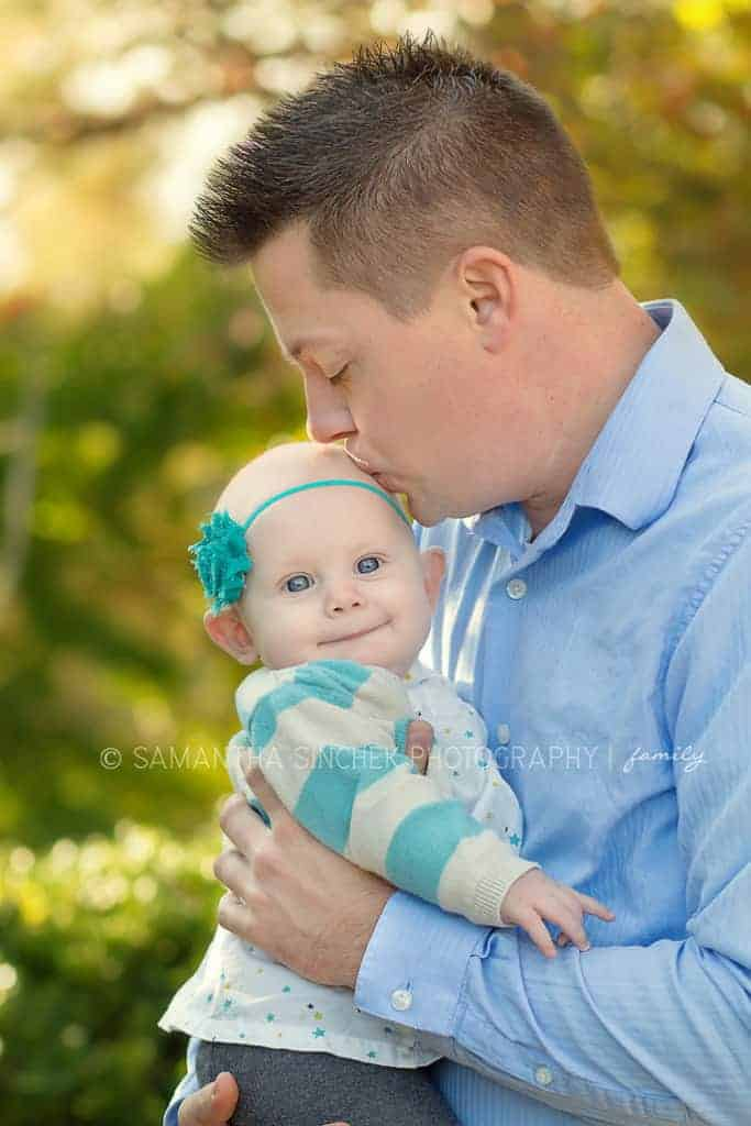 father kisses toddler girl on head at family session with samantha sinchek
