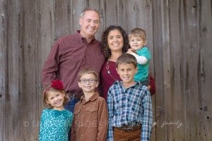family of 6 stands against old barn wood during family photo session