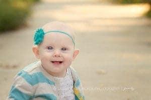 toddler girl sits on path wearing headbamd