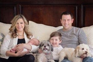 family sits on bed with dogs newborn during pictures