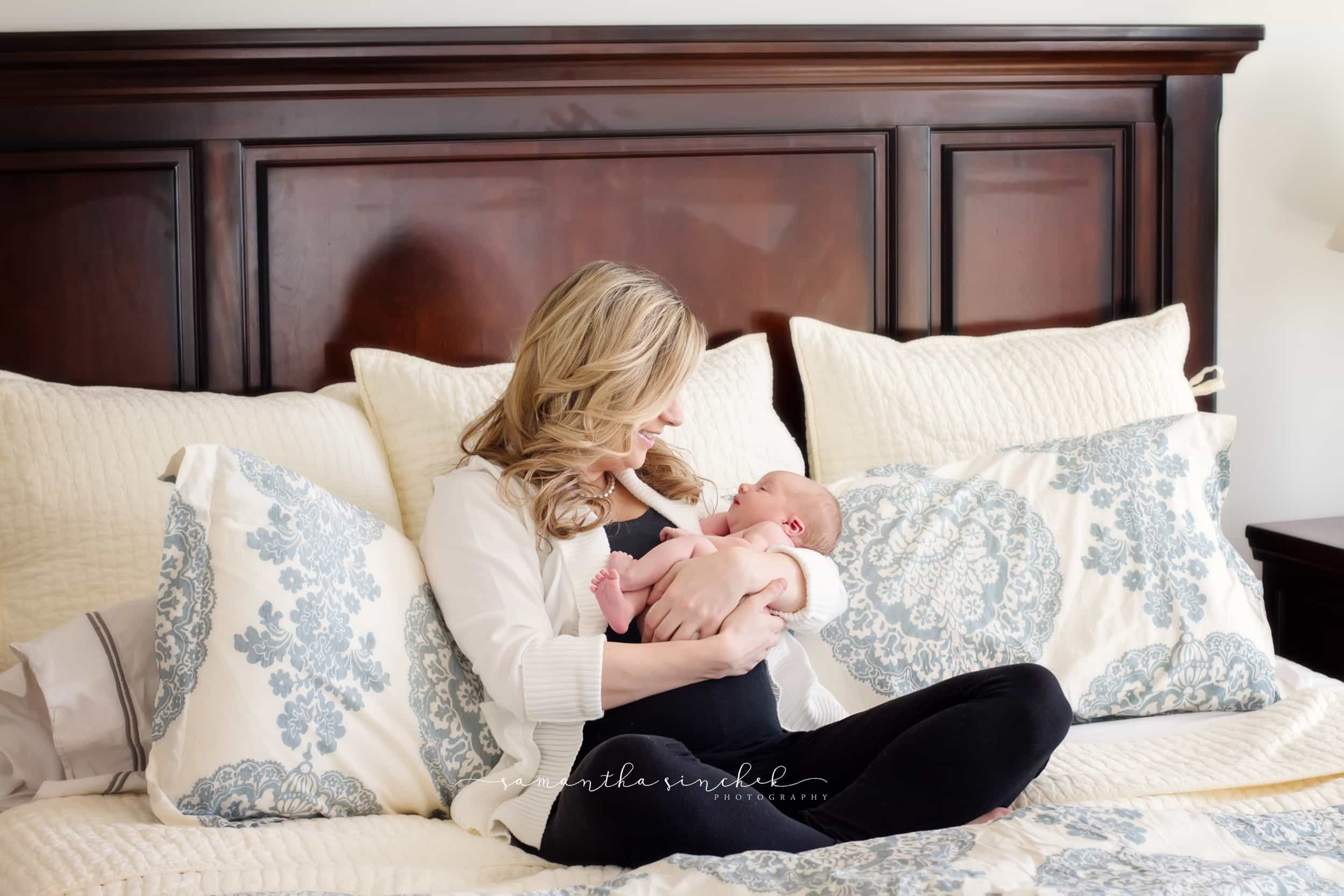 mother looks at newborn daughter during cincinnati newborn pictures