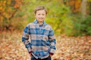 boy wearing plaid shirt smiles at camera