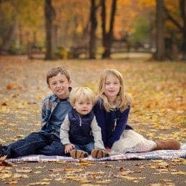 three siblings sit on path at sharon woods during family pictures