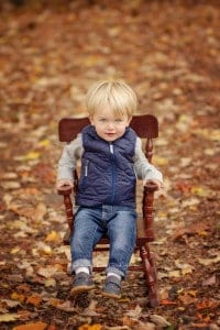 little boy sits in a rocking chair during pictures