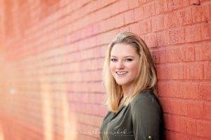Mason senior girl leans against brick wall in OTR Cincinnati