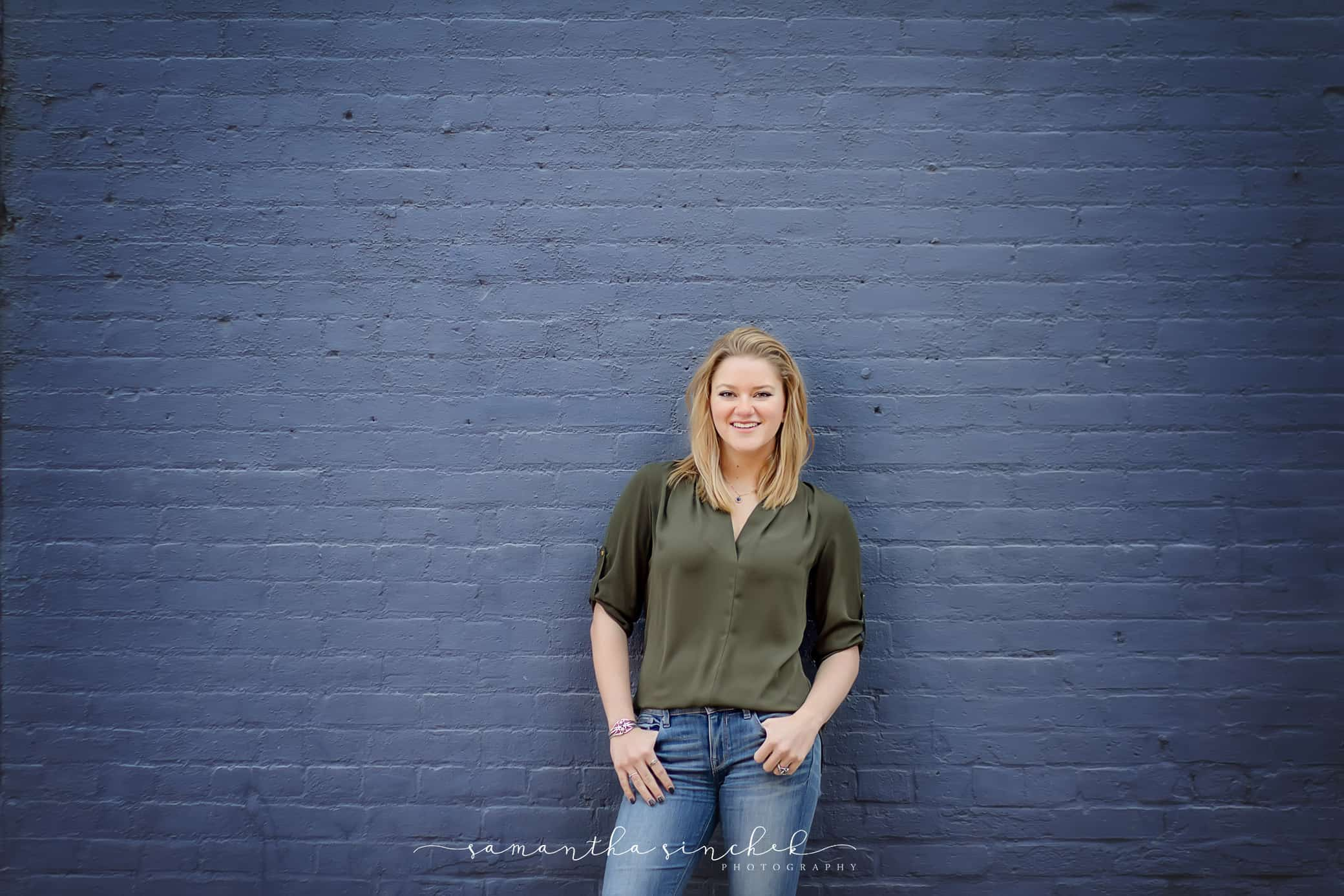 With fingers in her pockets a William mason high school senior stands against a blue brick wall