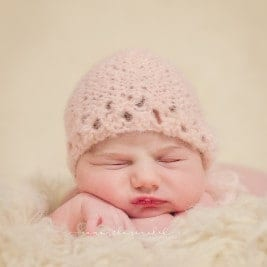 newborn from cincinnati ohio sleeps on fur wearing pink bonnet