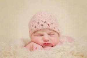 newborn from cincinnati ohio sleeps on fur wearing pink bonnet