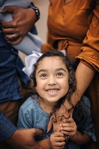 little girl smiles up at camera with her mom holding her hand at photos with cincinnati photographer Samantha Sinchek