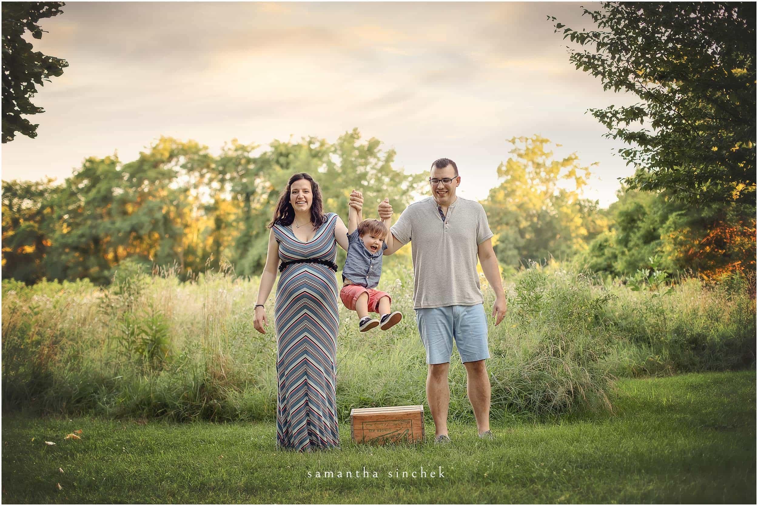 young family swing son at Glenwood gardens in cincinnati Ohio
