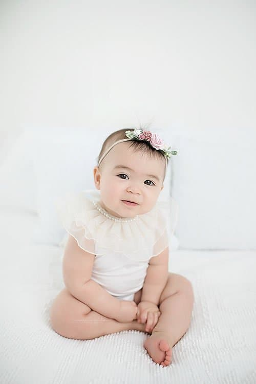 toddler sitting on bed at one year birthday pictures with Cincinnati photographer Samantha Sinchek